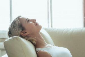 Kvinna i vit topp sitter i en soffa och vilar sitt huvud mot soffkudden