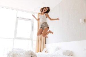 Kvinna i vit topp och shorts hoppar i sängen