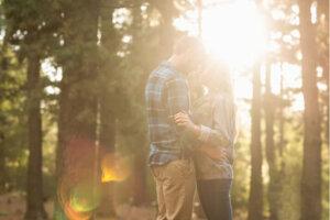 kvinna och man står nära varandra i skogen vid solnedgången
