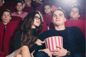 ungt par som sitter i biosalongen med popcorn
